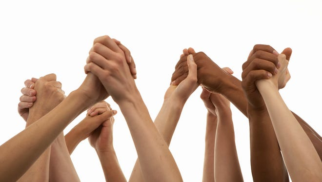 Several people with arms raised, holding hands, represent the type of human connection that begins with spiritual reflection.