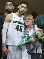 Valentine and his mother, Kathy Valentine, wait to be introduced to fans for Senior Day festivities after the Ohio State Buckeyes game March 5. Denzel is the jokester of the family, she said.