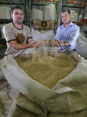 Adam Filippetti, founder and maltster, and his brother, Paolo Filippetti, founder and president, sift through a 1-ton tote of malting grains at Pioneer Malting Inc. in Chili.