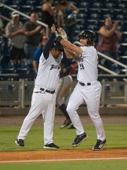 Taylor Sparks high fives the third base coach after hitting a walk-off home run in the bottom of the 11th inning during the Mississippi Braves vs. Blue Wahoos baseball game at Blue Wahoos Stadium in Pensacola, FL on Monday, July 11, 2016.