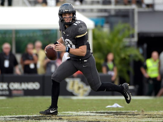 FILE - In this Nov. 10, 2018, file photo, Central Florida quarterback McKenzie Milton (10) rolls out to throw a pass during the second half of an NCAA college football game against Navy in Orlando, Fla. Milton and the Knights have feasted on overmatched foes for much of the season, but they face one of their toughest challenges Saturday when they host Cincinnati. (AP Photo/Phelan M. Ebenhack, File)
