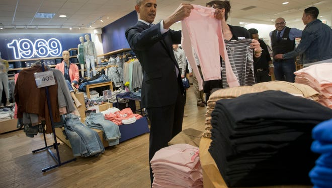 President Barack Obama, with the help of store employee Susan Panariello, shops for sweaters.