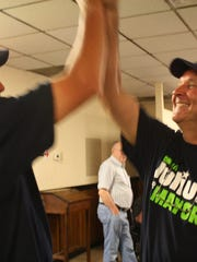 Democratic mayoral candidate Dennis Julius, right, receives a high five from supporter Jake Wheeler at a gathering at the Knights of Columbus in Jeffersonville after winning the primary.