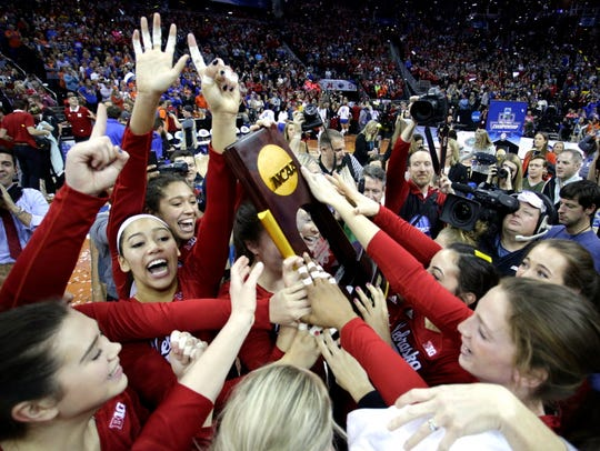 Nebraska players celebrate after winning the volleyball