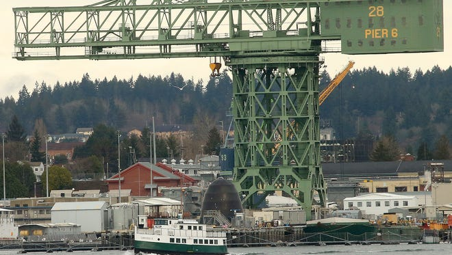The hammerhead crane at Puget Sound Naval Shipyard looms in the background as Kitsap Transit's Carlisle II heads for Port Orchard on Friday.