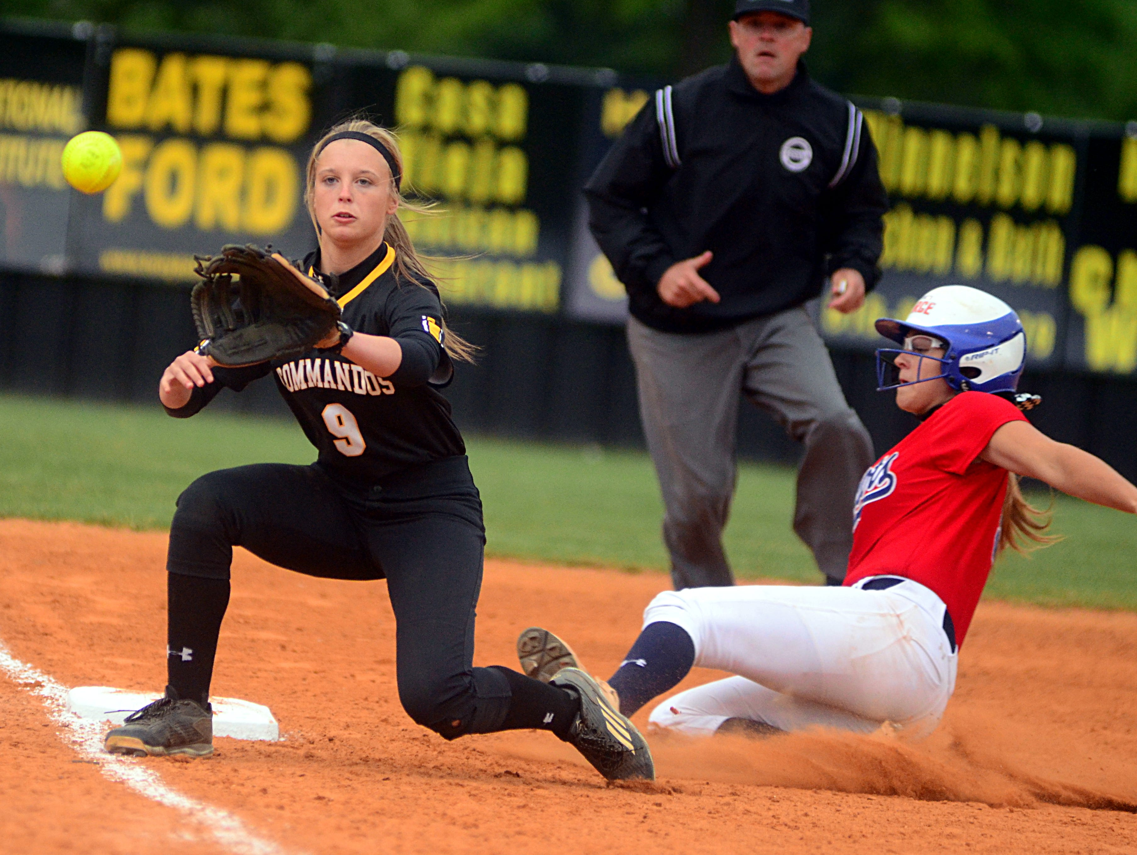 Hendersonville High junior third baseman M.J. Mattei receives a throw as Henry County sophomore Gracie Osbron slides into third base during the first inning of the Lady Commandos' 5-2 victory on Monday evening.