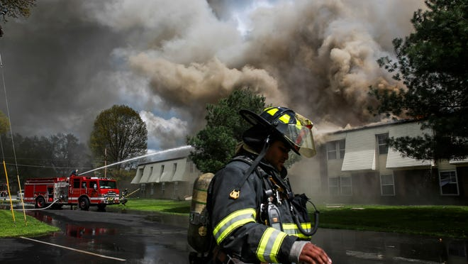 A Jeffersonville Fire Department fire fighter sprays from on top of a truck, left, as crews work to extinguish the spreading blaze at the Viking Drive apartments Thursday afternoon. A thick dark cloud of smoke surrouned the area from the massive fire consuming most of the south east building in the complex. April 16, 2015