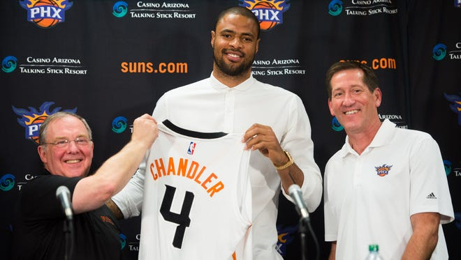Left to right, Lon Babby, President of Basketball Operations, Tyson Chandler, newest center for the Suns, and Jeff Hornacek, head coach of the suns, stand with Chandler as he holds up his new Suns jersey during a press conference. The Phoenix Suns held a press conference for their newest player, Tyson Chandler, at the U.S. Airways Center in Phoenix, AZ, on Thursday, July 9, 2015.