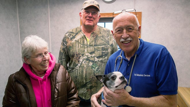 Veterinarian Jan Pol, right, poses with Mr. Pigglesworth and the dog's owners Loyd and Mable Frisbie.