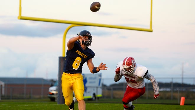 Pewamo-Westphalia's Jimmy Lehman, left, throws while being chased by Laingsburg's Tyler Bennett during the first quarter on Friday, Sept. 29, 2017, in Westphalia.