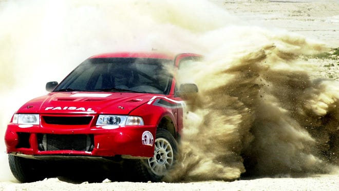 Qatar's Faisal al-Attiyah drives his Mitsubishi Lancer Evo 6 through the sand near Manama, Bahrain, in 2004
