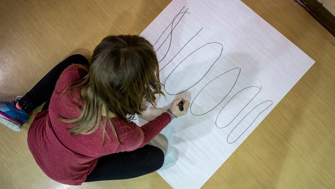 "Isabelle Driscoll, 10, writes out ""$10,000"" on a large piece of paper as she and other students prepare to reveal how much the school was awarded by a Campbell Soup contest Thursday, Feb. 2, 2017 at Keewahdin Elementary School."