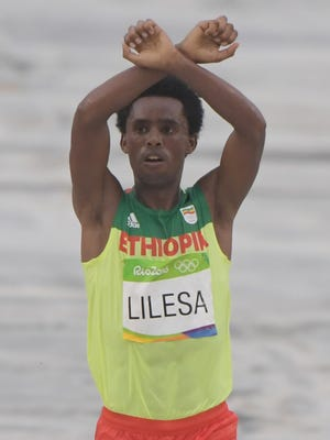 Feyisa Lilesa crosses the finish line to win the silver medal in the men's marathon on Sunday.