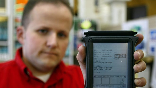 Chris Ludy, manager of a Big Red Liquor Store in Bloomington, Ind., shows the IDlogix, a hand held scanner that reads bar codes and electronic strips on the back of most states' drivers' licenses, Wednesday, Oct. 8, 2003.  Despite preventive measures, a steady stream of fake drivers licenses are sent to the United States each year, mostly from China.