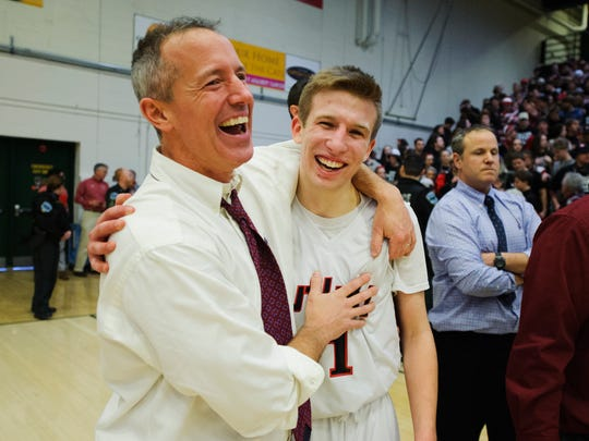 Rutland head coach Mike Wood and Rutland's Jack Morgan (11) celebrate at the conclusion of the Vermont state division I boys basketball championship game between the Mount Mansfield Cougars and the Rutland Raiders at Patrick Gym on Saturday afternoon March 17, 2018 in Burlington.