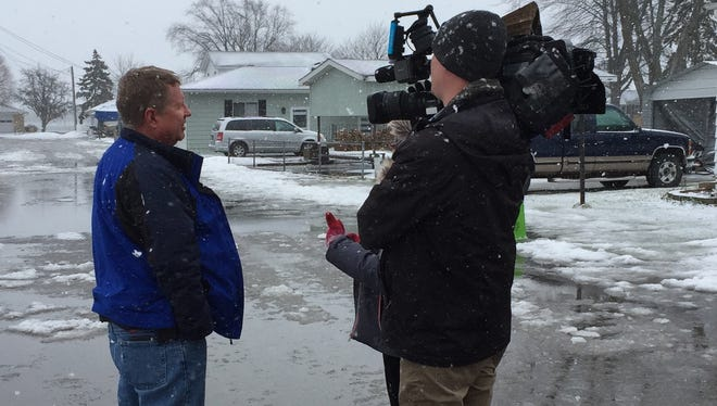 Jeff Friedland, county emergency management director, speaks with a TV crew about flooding in East China Township.