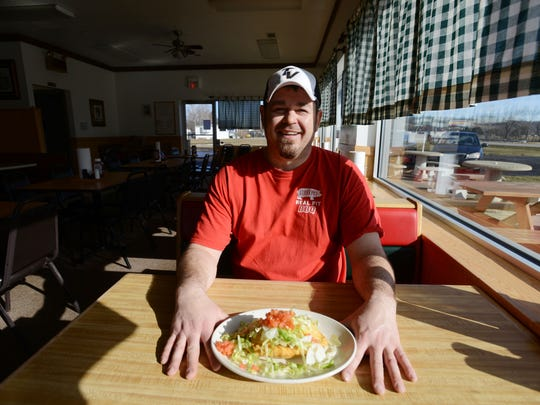 Russell Stachler, owner of Bill's Real Pit Bar-B-Q on Ohio 60 in Nashport, with one of the restaurant's sopapillas.