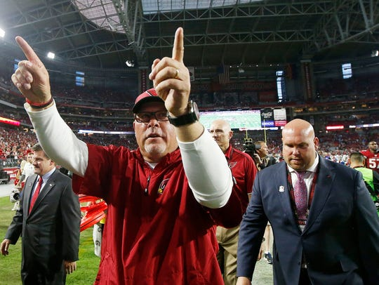 Arizona Cardinals coach Bruce Arians gestures to fans