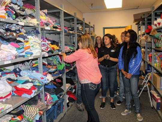 Children, Youth and Familes Department Investigations Supervisor Denise Narvaez gives a tour of the CYFD closet to Junior Leadership Otero advocates Monday.