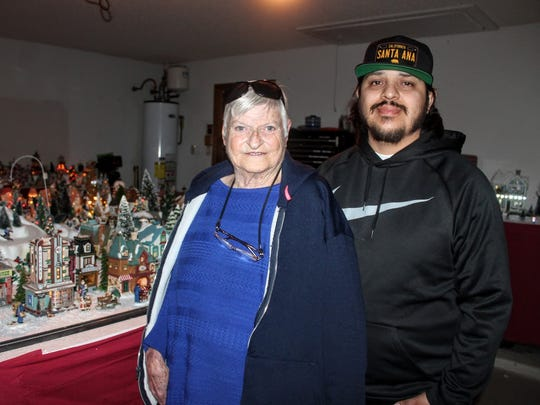 Sharon Jensen and her grandson Leo Torres, stand in front of their miniature Christmas village at 3211 Summer Ave.