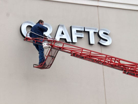 A crew member puts up a sign on the newly constructed Alamogordo Hobby Lobby at White Sands Mall Tuesday afternoon.