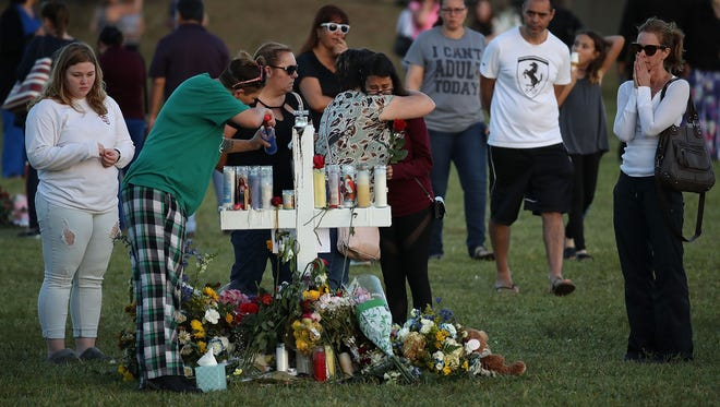 People visit a memorial at Pine Trails Park on Feb. 17, 2018, in Parkland, Fla.