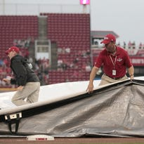 The grounds crew scrambles to remove the tarp for a 9:10 start after a two-hour rain delay.