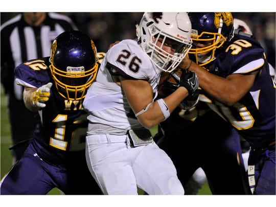 Brownwood High School running back Cain Kitrell is beset by Wylie High School's Jackson Smith (left) and Anthony Guerrero. Wylie won, 45-38.