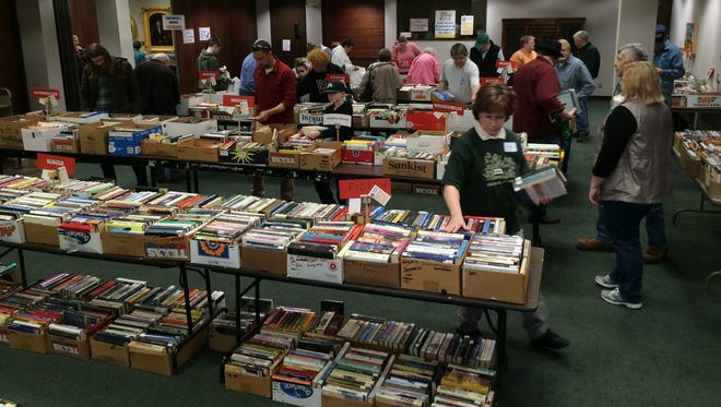 Books fill tables and overflow onto the floor as customers shop during a Friends of Morrisson-Reeves Library's book sale in the library's Bard Room.