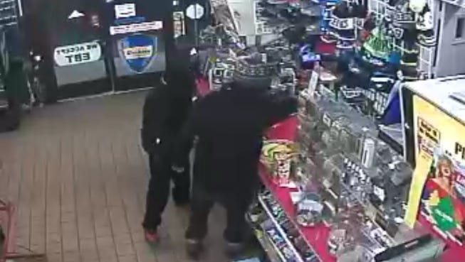 Gas station surveillance cameras show two suspects in the Wednesday night armed robbery.