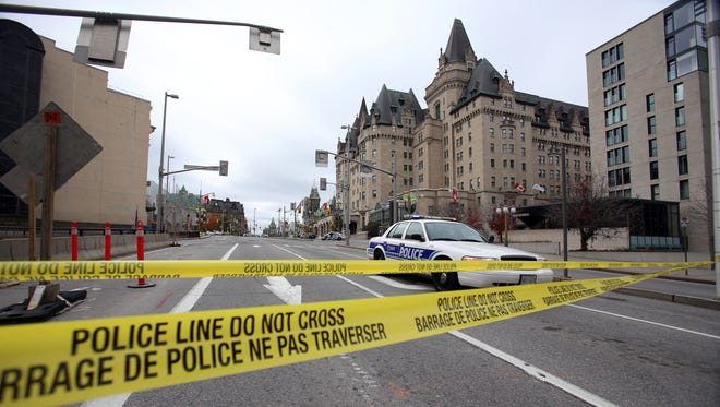 Police tape blocks Wellington St. at Sussex near the National War Memorial where a soldier was shot earlier in the day, just blocks away from Parliament Hill, on Oct. 22, 2014, in Ottawa, Canada.