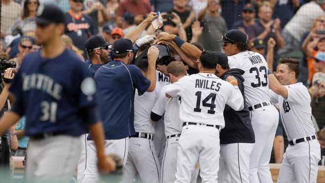 Seattle Mariners relief pitcher Steve Cishek (31) walks away as Detroit Tigers pinch runner Cameron Maybin is mobbed by teammates after scoring from third on a wild pitch during the 10th inning of a baseball game, Thursday, June 23, 2016, in Detroit. (AP Photo/Carlos Osorio)