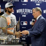 MLB commissioner Bud Selig presents San Francisco Giants pitcher Madison Bumgarner with the MVP trophy next to the Commissioner's Trophy after Game 7.