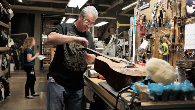 Martin employee working on the bridge of a guitar.