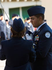 Mayfield Air Force JROTC Cadets Tiffany Cowger, left and Gio Hernandez, right, running the American flag up the pole in front of Mayfield High School, during a flag raising ceremony to remember the events of 9/11. Monday September 11, 2017.