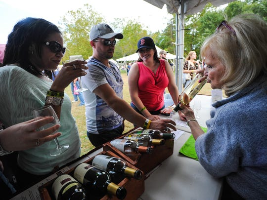 Faith Kirk of Fiore Winery and Distillery pours a sample glass for a round of event goers at the Salisbury Autumn Wine Festival on Saturday afternoon in Permberton Park.