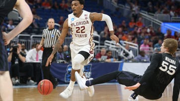 FSU's Xavier Rathan-Mayes drives past a falling J.P. Macura of Xavier during the NCAA Tournament's second round at the Amway Center in Orlando on Saturday, March 17, 2017.
