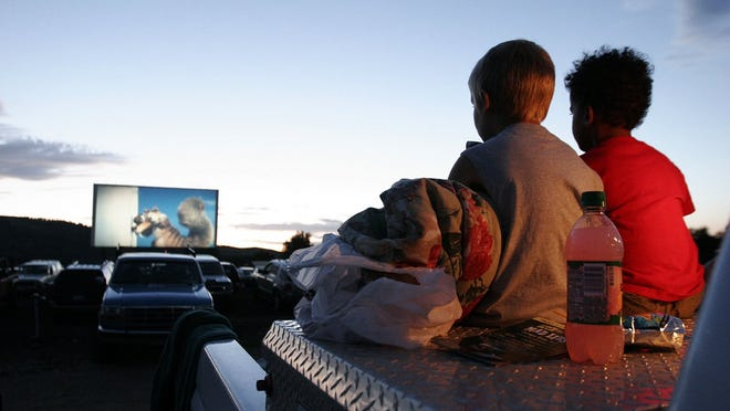 --07-17-2005, C1\Sam Woffort, left, and Benjamin Nortey, both 5, find a comfortable seat on the bed of a pickup as the sun sets and the previews begin at the Holiday Twin Drive-In.Photos by Bradley Wakoff--Sam Woffort, left, and Benjamin Nortey, right, both 5, find a comfortable seat on the bed of a pickup as the sun sets and the previews begin at the Holiday Twin Drive-in in Fort Collins, July 10, 2005.