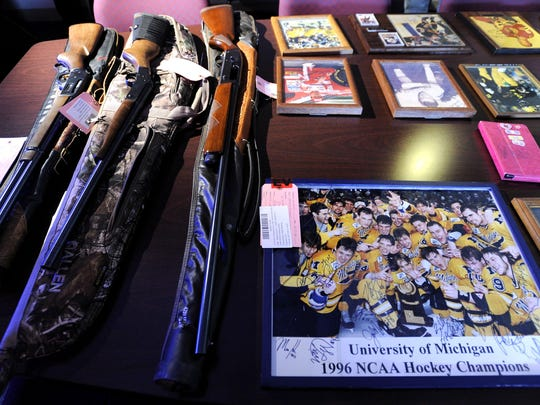 These are recovered stolen items, including, from left: a Lorcin L25 .25-caliber semi-automatic pistol, a Marlin lever action .35-caliber Remington, a New England Firearms Handi-Rifle SB2, a Remington 16-gauge semi-automatic shotgun, and a signed group shot of the Michigan 1996 NCAA hockey champions.