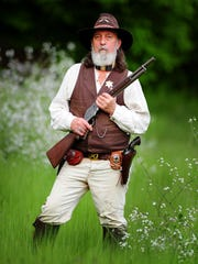 """Tom """"PaleWolf Brunelle,"""" aka Tom Rickman, holds a 1887 Winchester 12-gauge shotgun at his home in Sublimity. Rickman recently was inducted into the Cowboy Action Shooters Hall of Fame."""