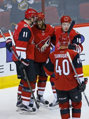 Arizona Coyotes left wing Anthony Duclair (10) is greeted by teammates Martin Hanzal (11), Max Domi and Alex Tanguay following his power play goal against the Calgary Flames during the second period of their NHL game Monday, March 28 2016 in Glendale, Ariz.