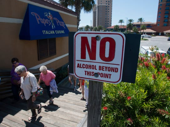 Escambia County Commissioners have voted to fund a $15,000 survey to gauge response to the ordinance banning alcohol on Pensacola Beach's boardwalk area.