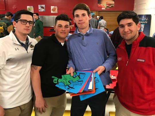 Player exchange puzzle pieces during Autism Awareness Baseball Challenge reception.
