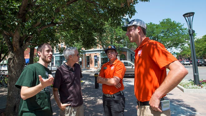 Downtown ambassadors Jake Fraley and Chance Lachowitzer speak with David and Chris More Friday. The two patrol the Old Town area providing maps and advice for shops, dining and visiting Fort Collins.