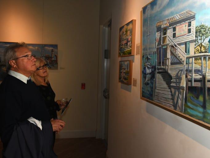 Steve and Sally Bataran look over paintings of the