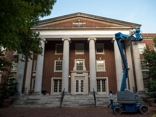 Workers cover up the name on the exterior of Confederate