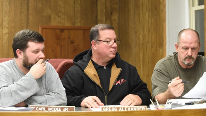 Marion County Quorum Court members Carl McBee Jr., left, Gregg Alexander and Bill Stahlman, Jr. discuss an ordinance amending numbers and compensation of county employees during the final 2015 meeting.