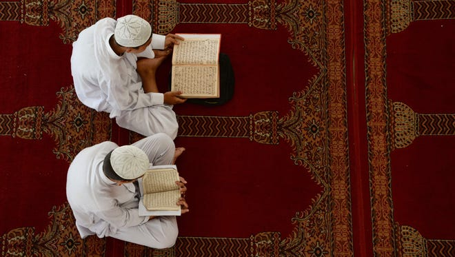 Afghan boys study the Koran during the Islamic holy month of Ramadan at a mosque in Jalalabad last year.