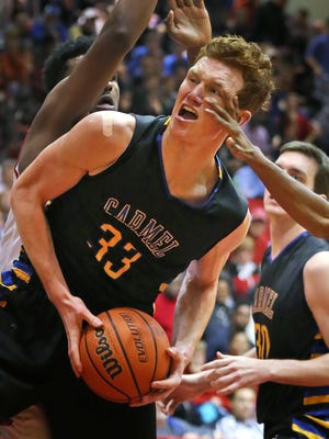 Carmel's #33 John Michael Mulloy gets a hand in his face as he drives during second half action of the Carmel at North Central High School boys basketball game, Friday, December 16, 2016.  North Central won 59-45.