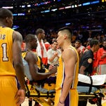 Lakers forward Julius Randle (30) shakes hands with guard Jeremy Lin (17) after an injury during the second half Tuesday against Houston.